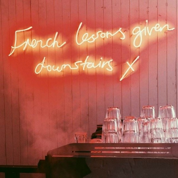 A neon sign hanging in the Soho Grind location.