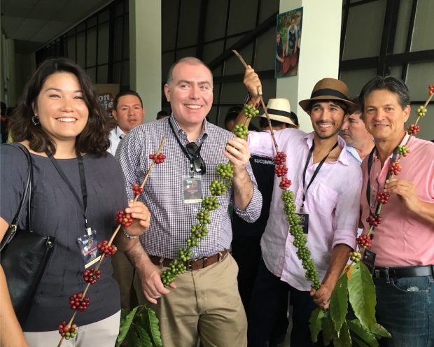 International judges posing with robusta branches.