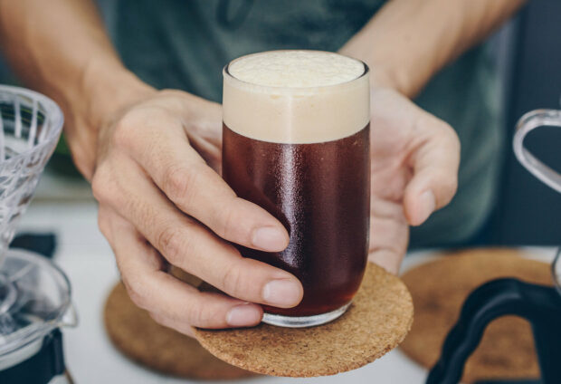 Barista holding and serving a drinking glass of cold brew dip coffee.